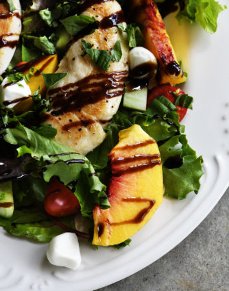Grilled Chicken and Peach Salad Recipe - A light and delicious dish that is perfect for lunch or dinner. Made with grilled chicken, fresh juicy peaches, and topped with tangy balsamic. // addapinch.com