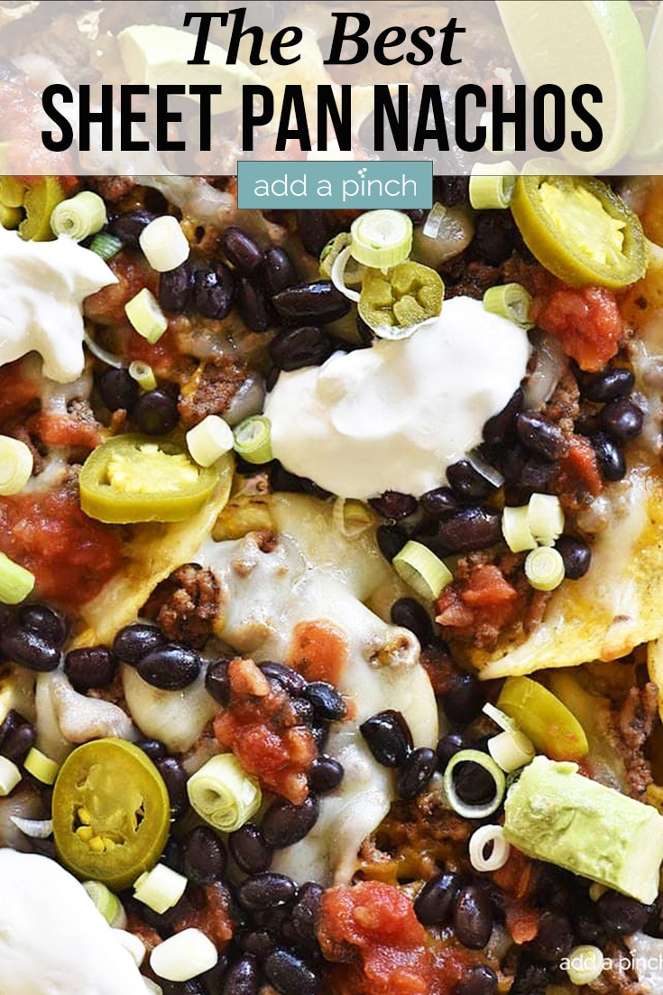Sheet Pan Nachos topped with sour cream, avocados and more - with text - addapinch.com