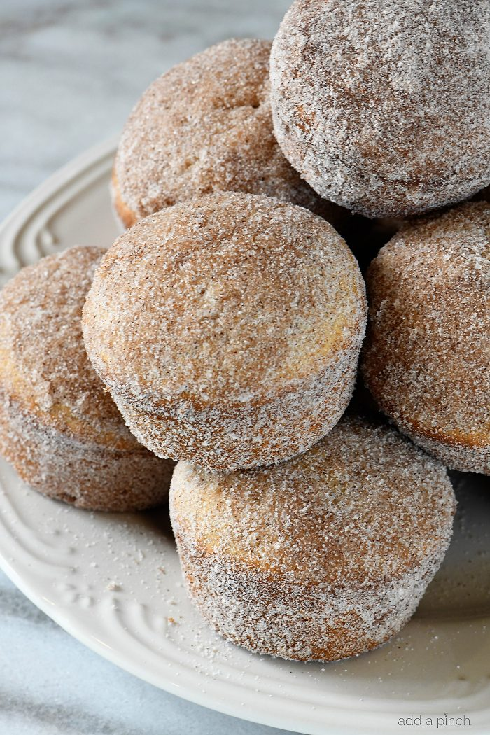 Apple Cider Donut Muffins Recipe - These apple cider muffins are light, fluffy and coated in an amazing cinnamon sugar coating! // addapinch.com