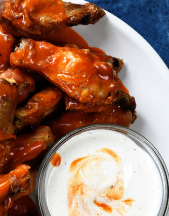 Baked Crispy Buffalo Chicken Wings Recipe - Crispy buffalo wings no longer have to be deep fried to be delicious! This easy recipe for baked chicken wings makes everyone's favorite wing even better! // addapinch.com