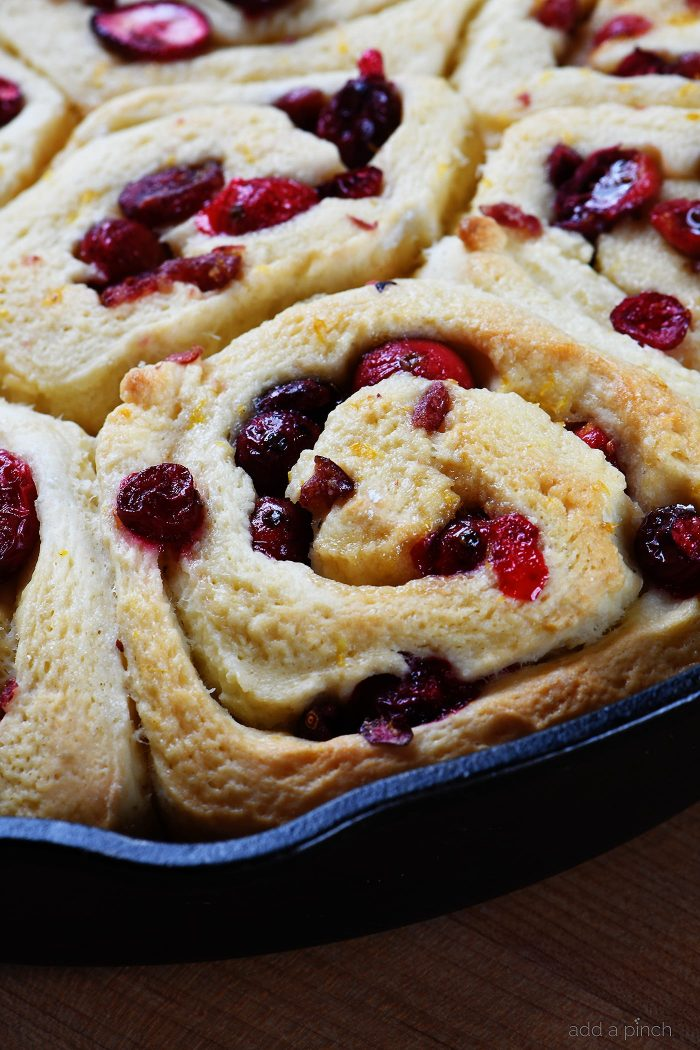 Cranberry Orange Rolls Recipe - The perfect blend of sweet and tart comes together in these easy Cranberry Orange Rolls! Topped with Orange Cream Frosting! // addapinch.com