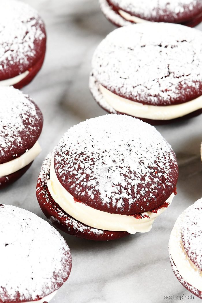 Red Velvet Cookies Recipe - These delicious cookies taste like your favorite red velvet cake in cookie form! Red Velvet cookies filled with cream cheese frosting and topped with a magical dusting of confectioner's sugar! // addapinch.com