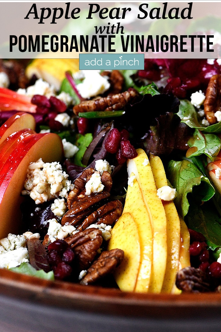 Apple Pear Salad with roasted pecans, blue cheese crumbles, and salad greens drizzled with Pomegranate Vinaigrette served in a wooden salad bowl - with text - addapinch.com