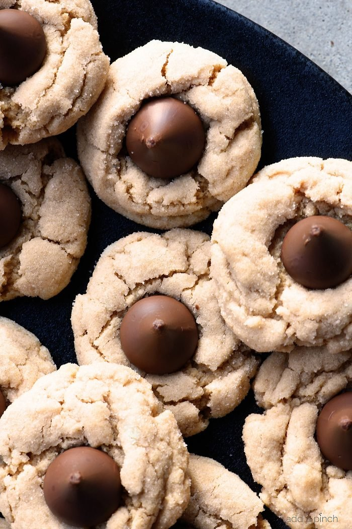 Peanut Butter Blossoms Recipe - This soft classic peanut butter cookie topped with a milk chocolate kiss is always a favorite! // addapinch.com