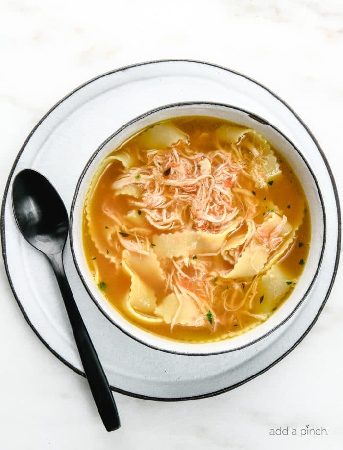 Overhead photograph of a bowl of chicken noodle soup in a white bowl with a black rim on a white plate with a black rim.