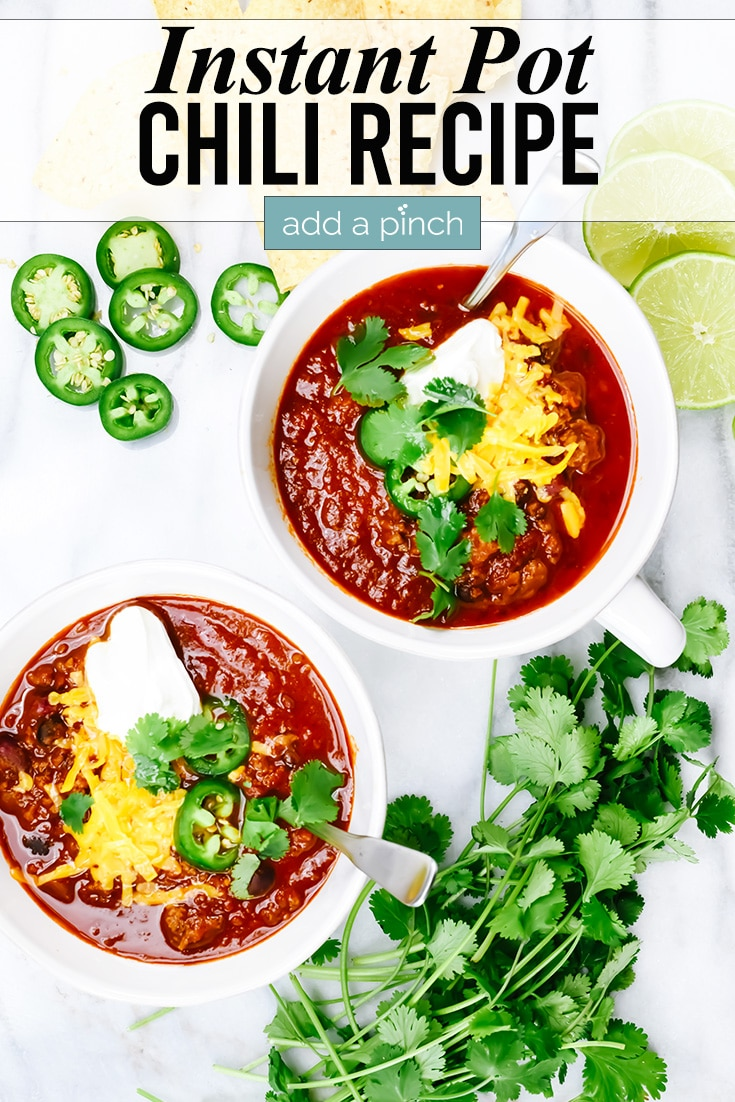 Two bowls of Instant Pot Chili garnished with cheese, sour cream and jalapenos, with sliced jalapenos and garnish on the table - with text - addapinch.com