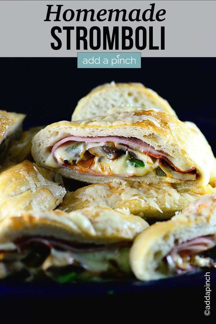 Freshly baked Stromboli filled with meat, cheeses, and vegetables, stacked on a serving tray - with text - addapinch.com