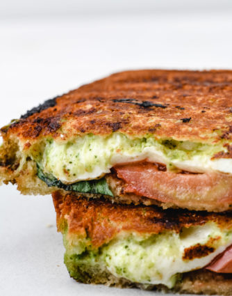 Caprese Grilled Cheese Sandwich Recipe - A delicious, gourmet grilled cheese made of sourdough, pesto, mozzarella, tomatoes, and fresh basil. // addapinch.com