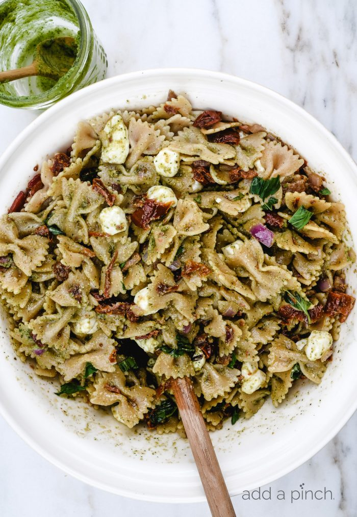 Pesto Caprese Pasta Salad Recipe - A classic pasta updated with a bright pesto dressing, sundried tomatoes, and bacon. A perfect quick and easy side dish! // addapinch.com