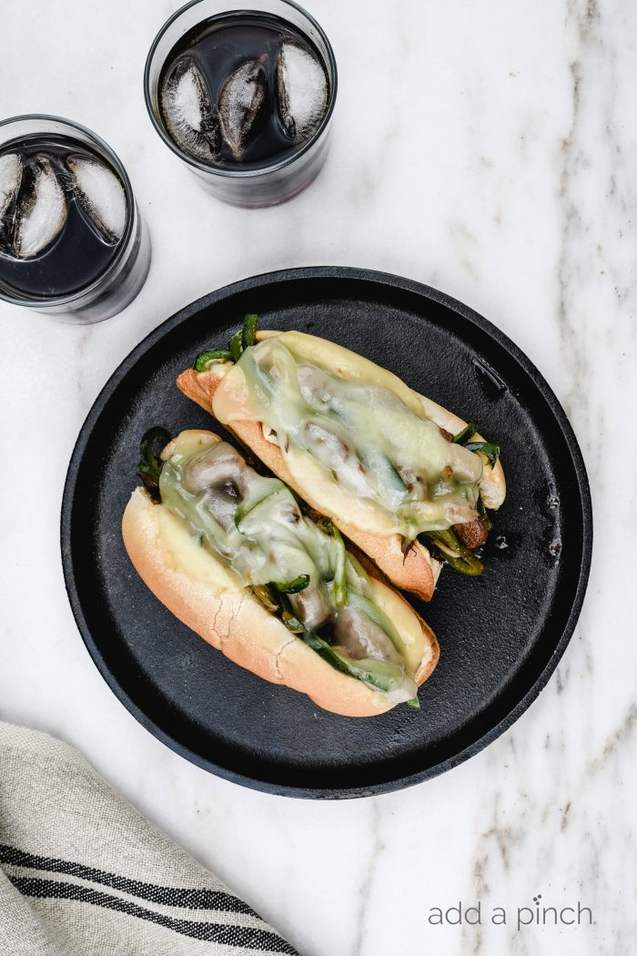 Philly Cheesesteak Recipe - Philly Cheesesteak Recipe - A Classic cheesesteak recipe made of seasoned, thinly sliced beef, peppers, onions, and lots of cheese! Ready in 30 minutes! // addapinch.com
