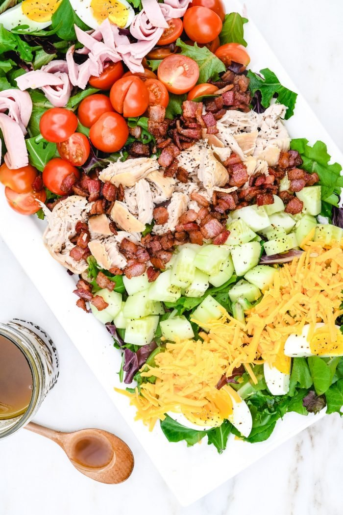 This Easy Chicken Club Salad Recipe is a delicious twist on the favorite layered club sandwich. Made of tender chicken, bacon, tomatoes, and so much more! It is always a favorite! // addapinch.com