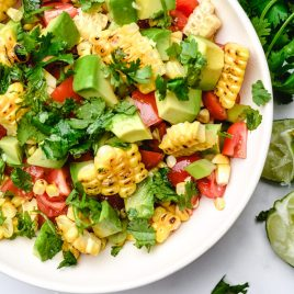 Grilled corn salad features fresh summer corn with avocado, tomato, jalapeno, and onion. A delicious, quick, easy and healthy recipe that is perfect for summer barbecues! // addapinch.com