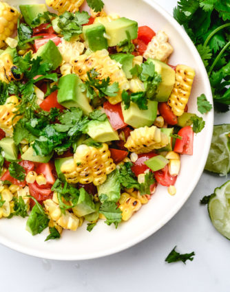 Grilled corn saladfeatures fresh summer corn with avocado, tomato, jalapeno, and onion. A delicious, quick, easy and healthy recipe that is perfect for summer barbecues! // addapinch.com