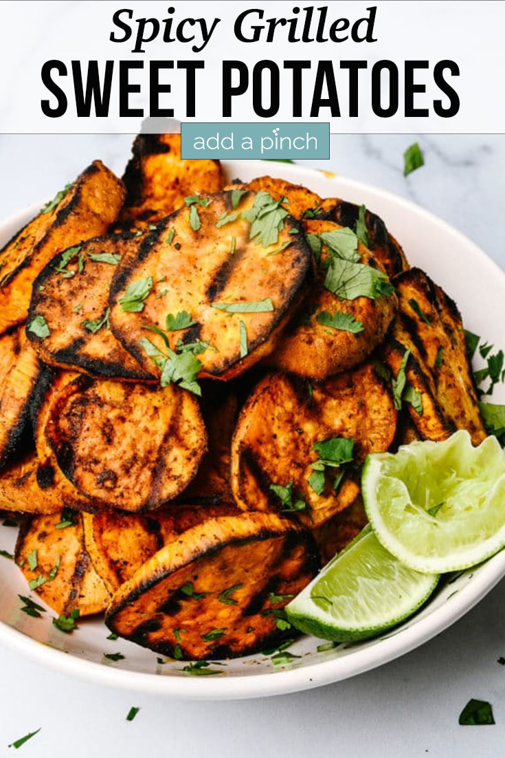 Stack of sliced Spicy Grilled Sweet Potatoes on white plate, with lime slices and green herbs as garnish - with text - addapinch.com