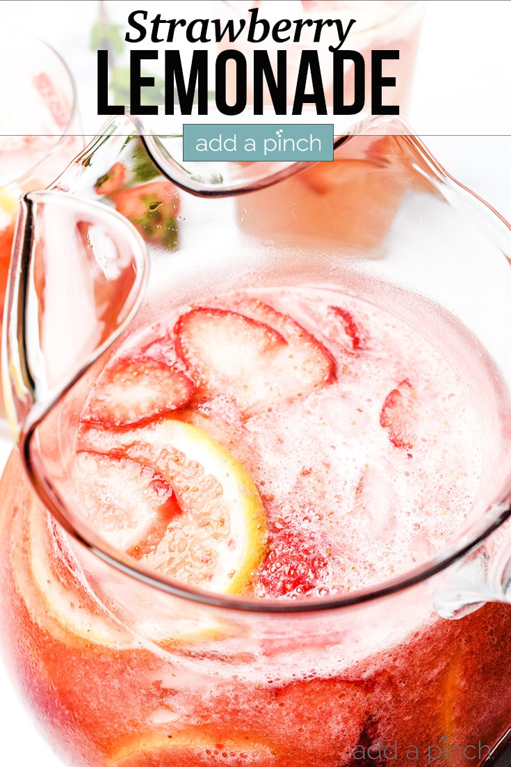 Strawberry Lemonade in glass pitcher and in glasses, garnished with strawberries and lemon slices - with text - addapinch.com