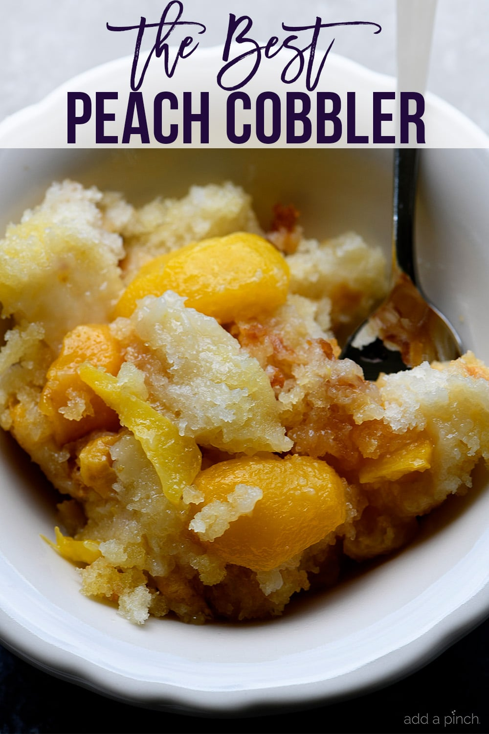 Bowl of Easy Peach Cobbler with spoon - with text - addapinch.com
