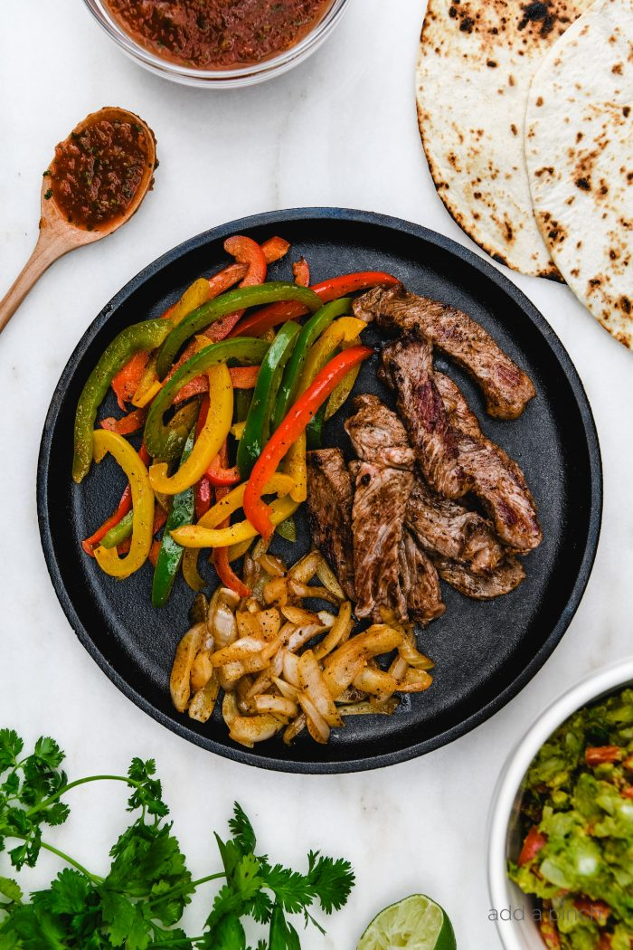 Ribeye Fajitas with peppers, onions, and served with tortillas, guacamole, and restaurant style salsa. // addapinch.com