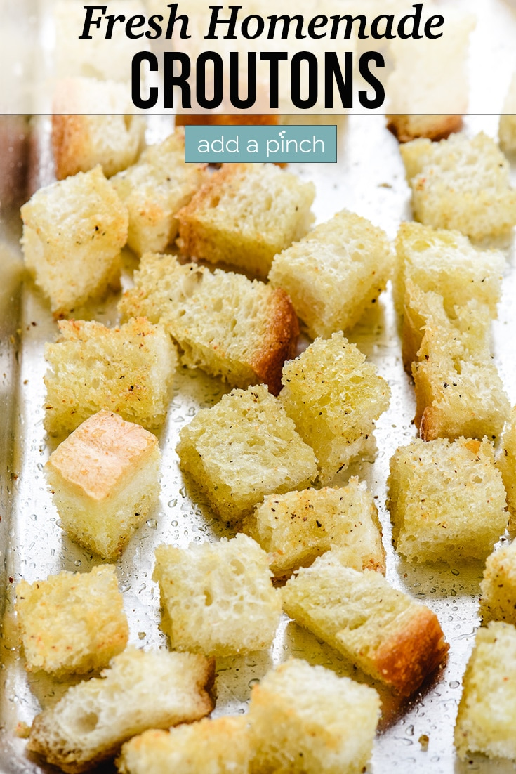 Fresh Homemade Croutons on a baking sheet - with text - addapinch.com