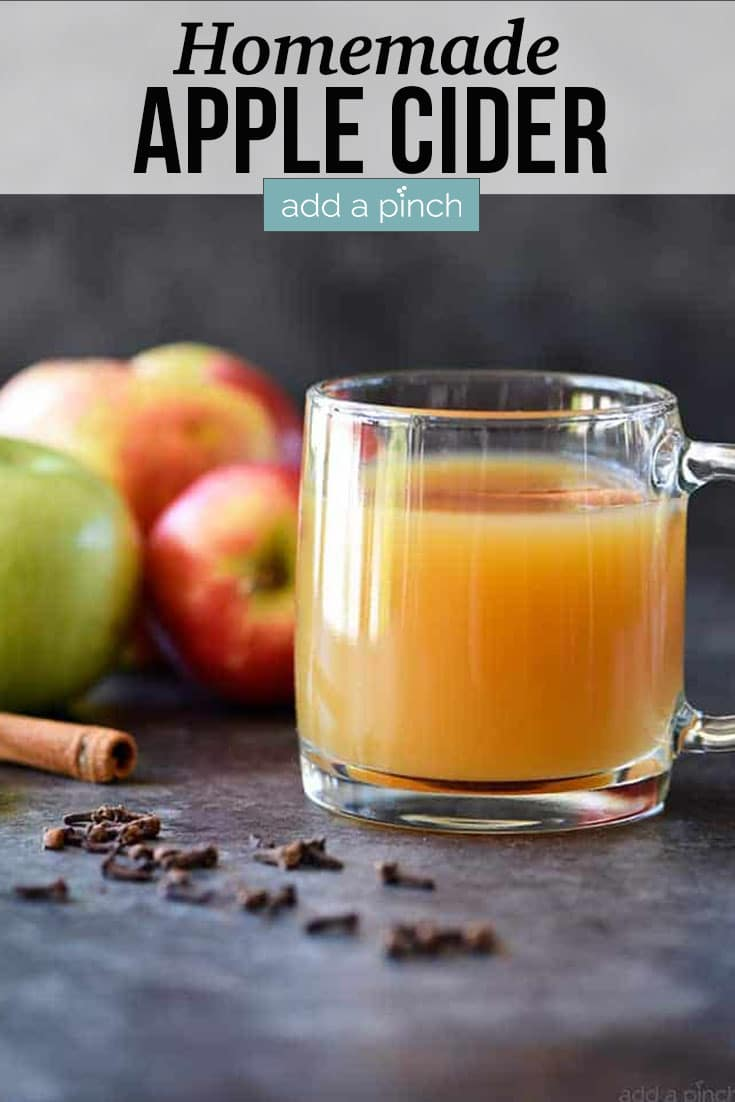 Glass mug of Homemade Apple Cider surrounded by fresh apples, cinnamon sticks and cloves - with text - addapinch.com