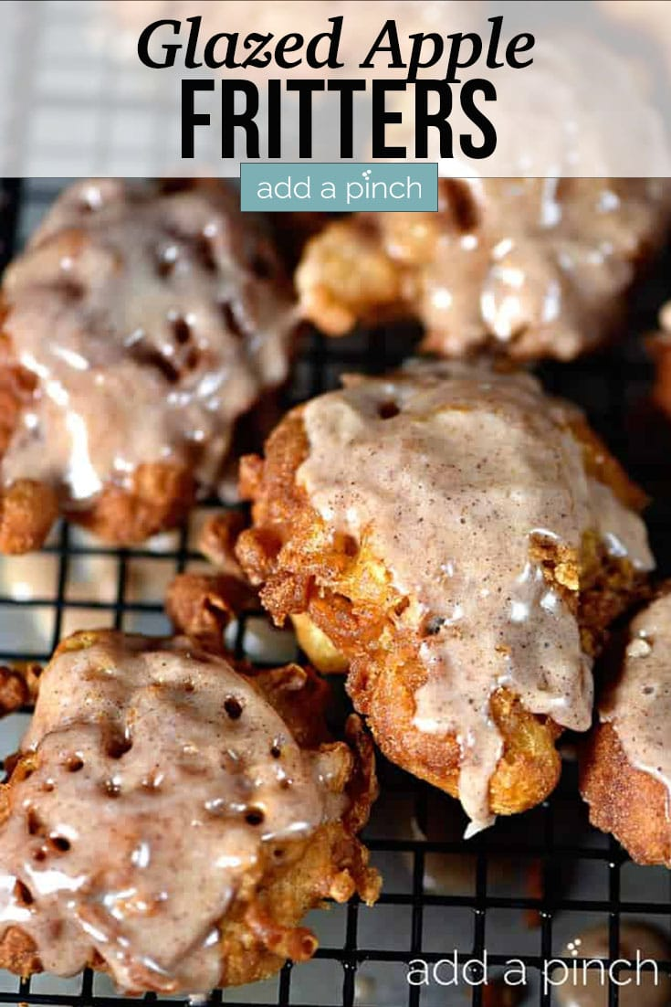 Tray of golden brown Apple Fritters drizzled with glaze - with text - addapinch.com