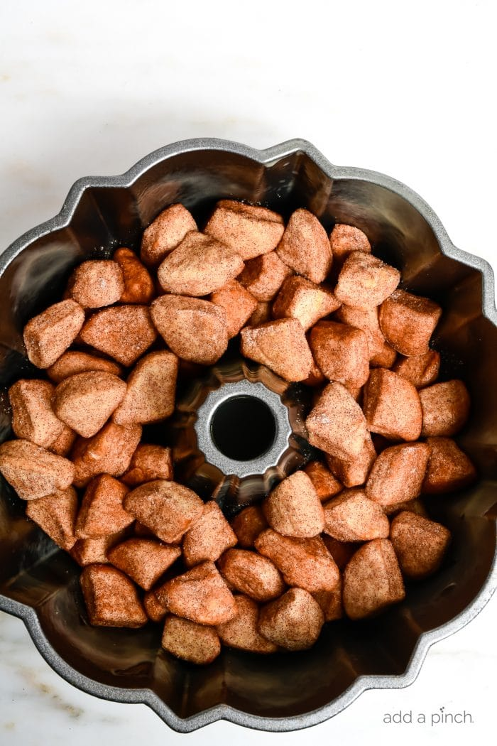 Photograph of monkey bread before it has been baked. Shown in a bundt pan on white marble. // addapinch.com