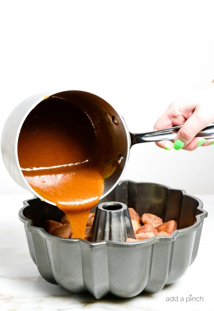 Photograph of caramel pouring over unbaked monkey bread in a bundt pan ready to go in the oven for baking. // addapinch.com
