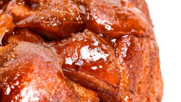 photograph of golden brown monkey bread with a caramel glazed on a white platter. // addapinch.com