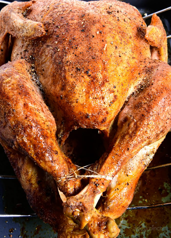 Photo of a roasted turkey on a roasting pan simply seasoned with salt and pepper. // addapinch.com