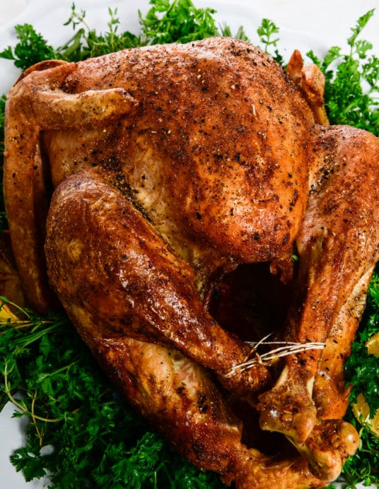 Photograph of golden brown roasted turkey served on a white platter with fresh herbs.