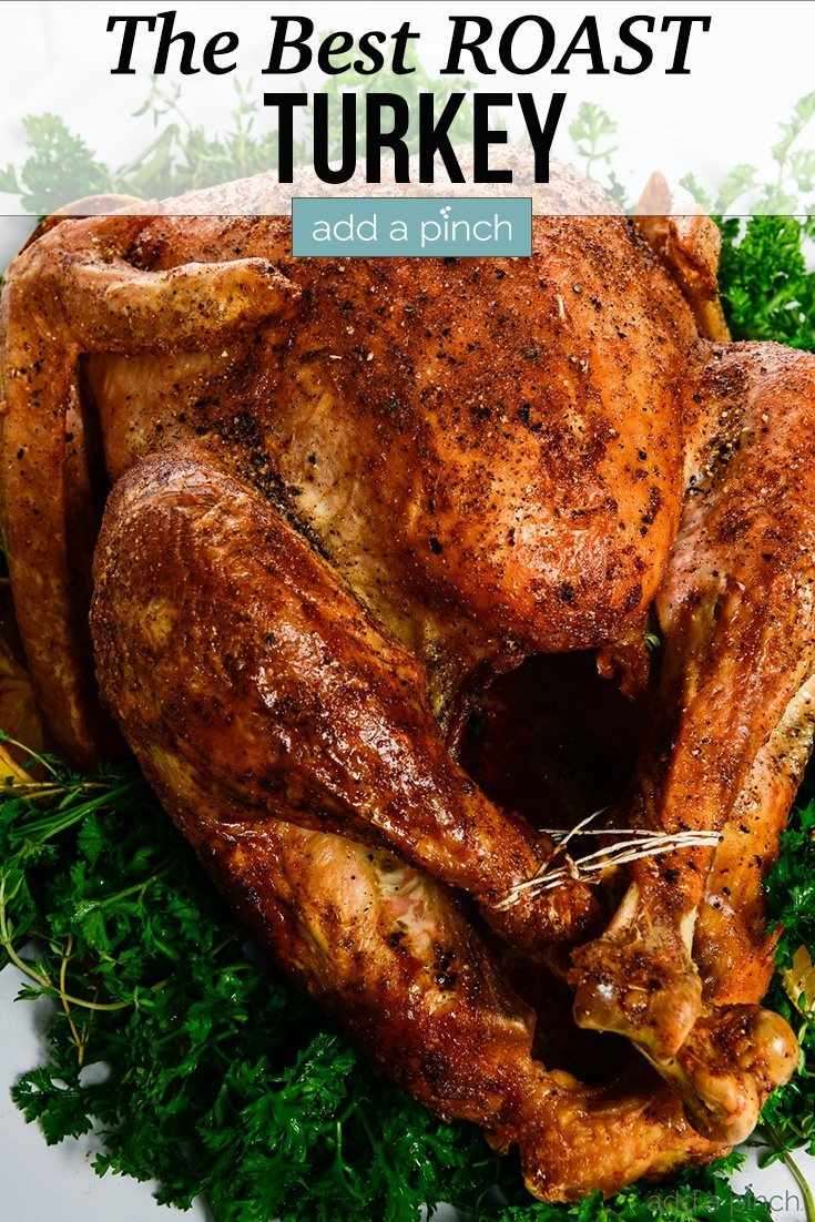 Golden brown Roast Turkey on platter with green herbs - with text - addapinch.com