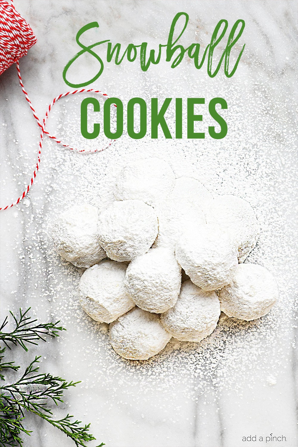 Stack of Snowball Cookies on marble board surrounded by ribbon and greenery - with text - addapinch.com