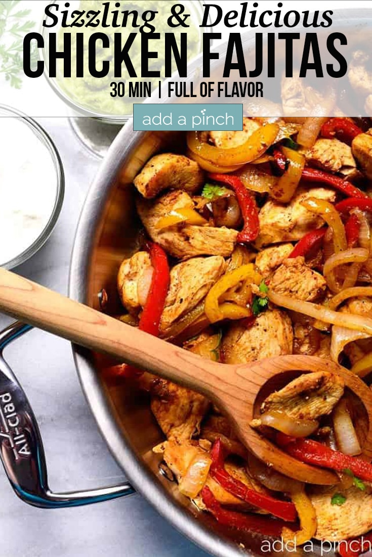 Chicken Fajitas in a stainless skillet with wooden spoon - with text - addapinch.com