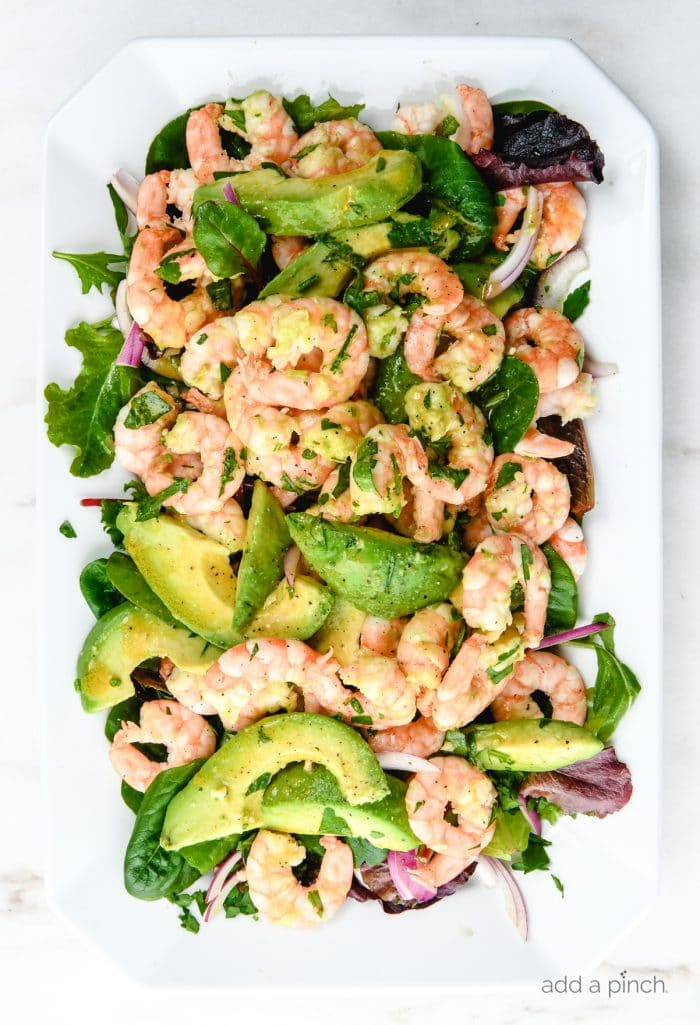 Photograph of citrus shrimp avocado salad on a white platter on white marble. // addapinch.com