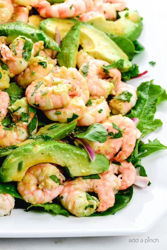 Close up photograph of citrus shrimp avocado salad on a white platter. // addapinch.com