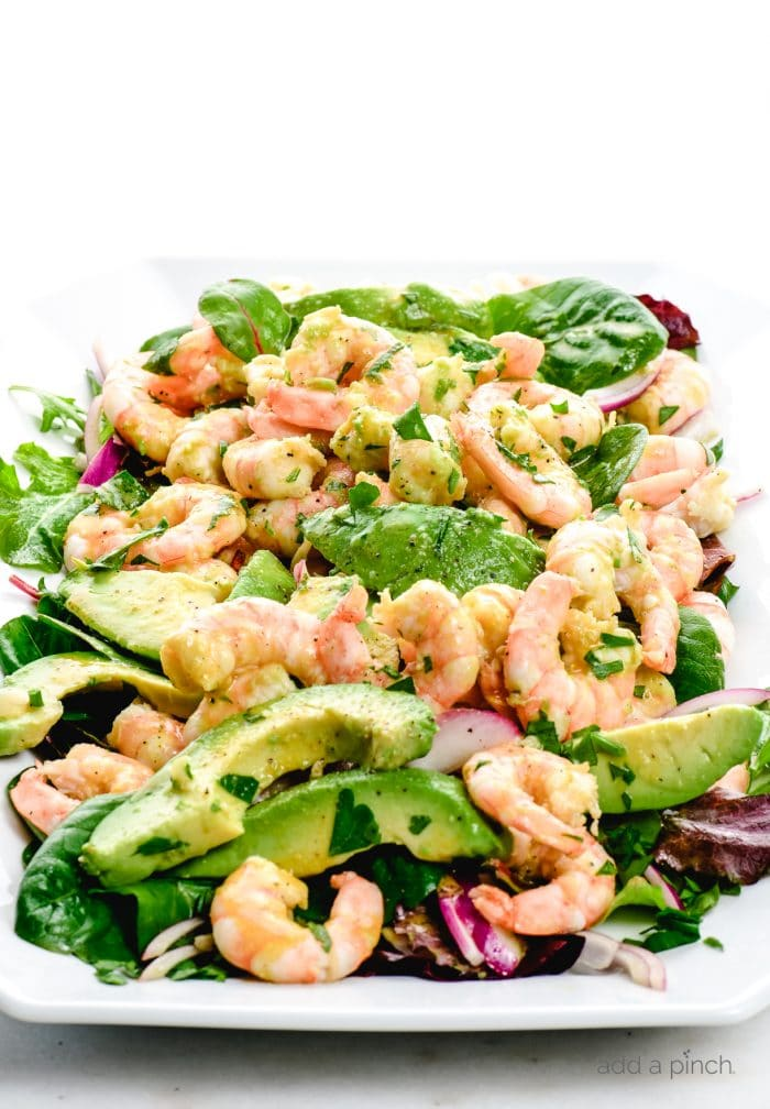 Photograph of white platter filled with citrus shrimp avocado salad with red onions.