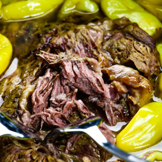 Photograph of Mississippi Roast with pepperoncini peppers in a slow cooker.