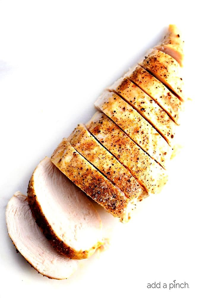 Sliced Baked Chicken Breast diagonally on a white board
