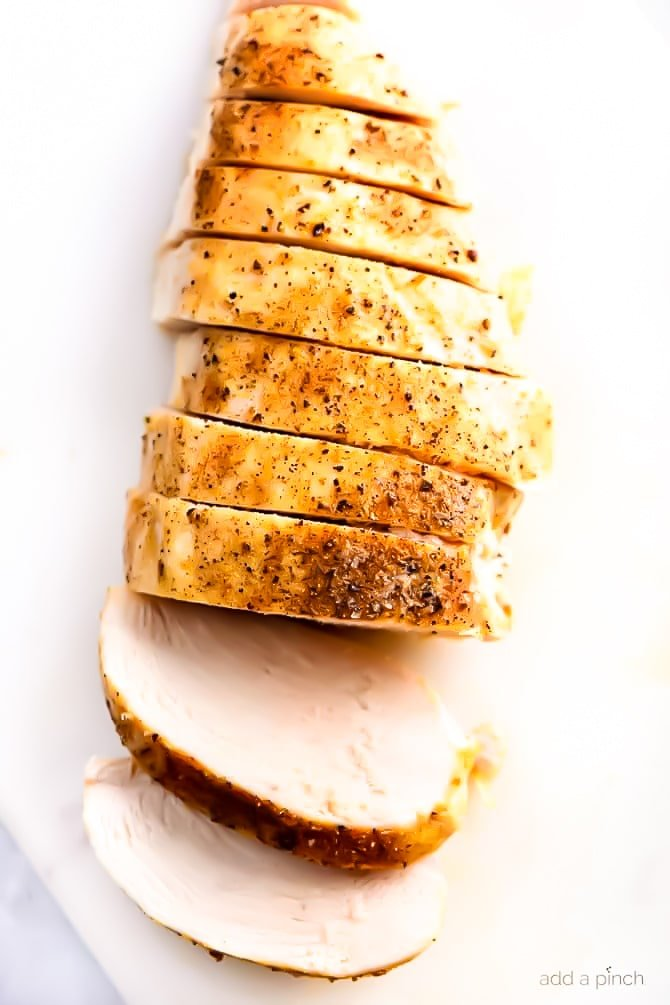 Juicy baked chicken breast is sliced and served on a white plate // addapinch.com #bakedchickenbreast #chickenbreastrecipe #chickenbreast