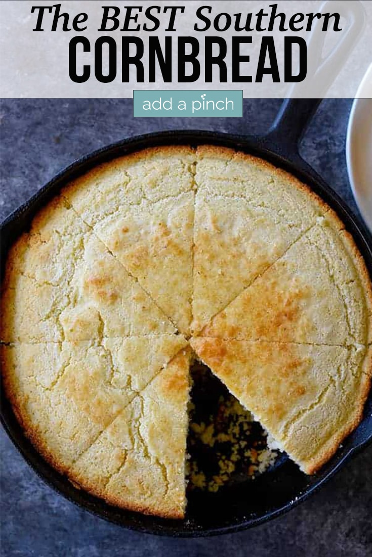 Southern Cornbread in a cast iron skillet with one wedge cut - with text - addapinch.com