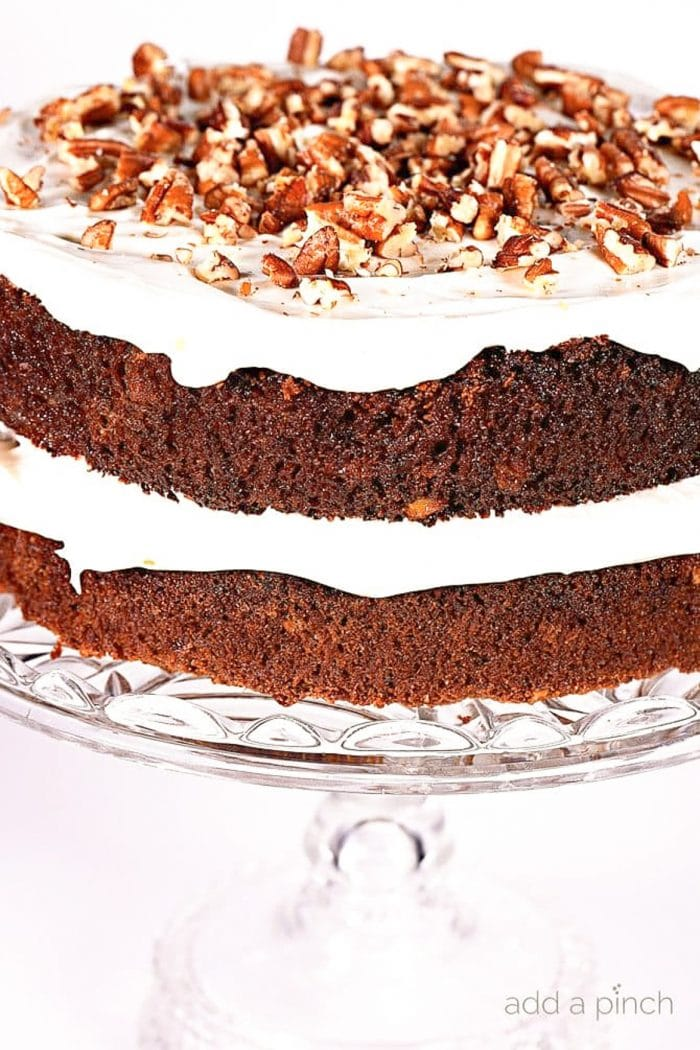 Layered carrot cake with cream cheese frosting and topped with roasted pecans | addapinch.com