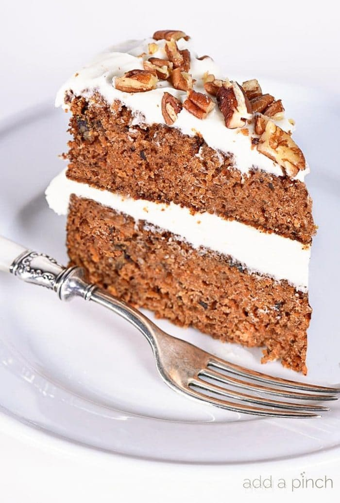 Slice of carrot cake with cream cheese frosting and topped with roasted pecan pieces on a white plate with a silver fork. | addapinch.com