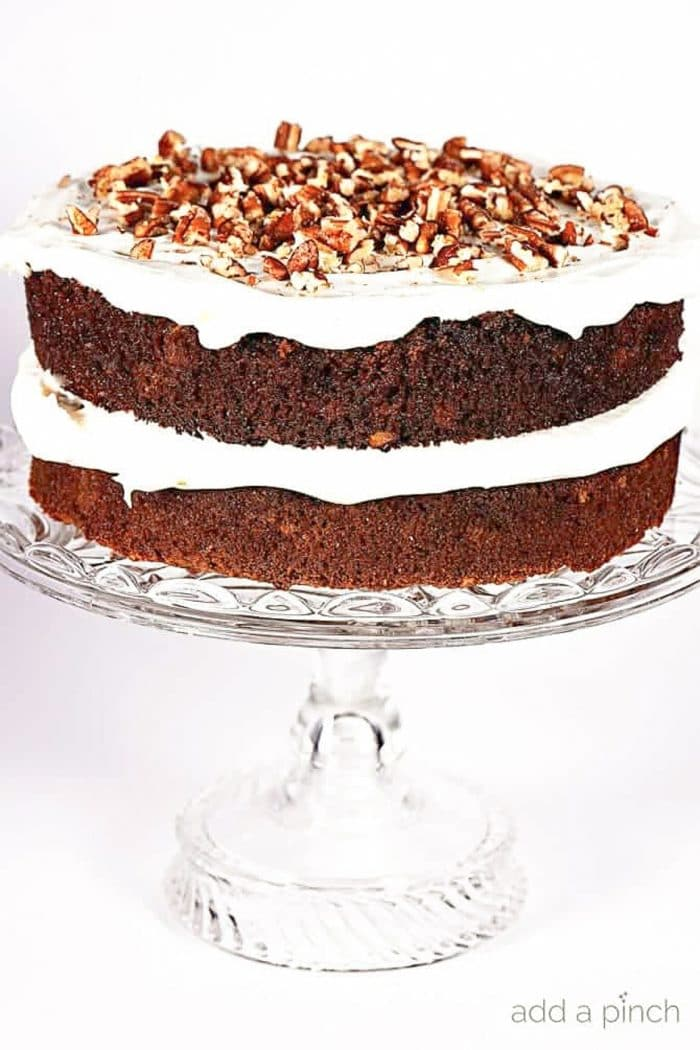 Layered carrot cake with cream cheese frosting topped with roasted pecan pieces on a fancy clear glass cake stand on a white background | addapinch.com