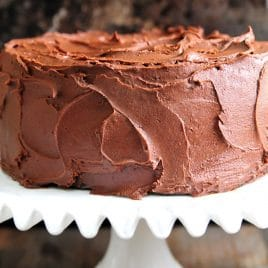 Chocolate Cake with Chocolate Buttercream Frosting on a white cake plate and dark background.