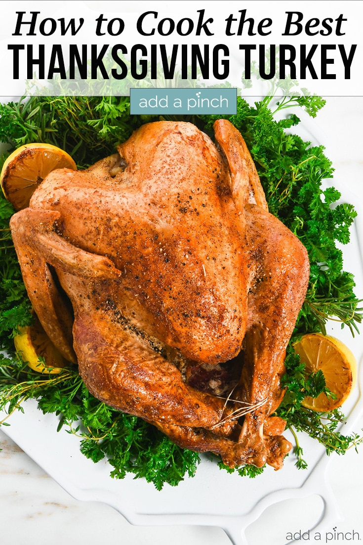 Roast Turkey on platter adorned with green herbs and roasted lemons - with text - addapinch.com