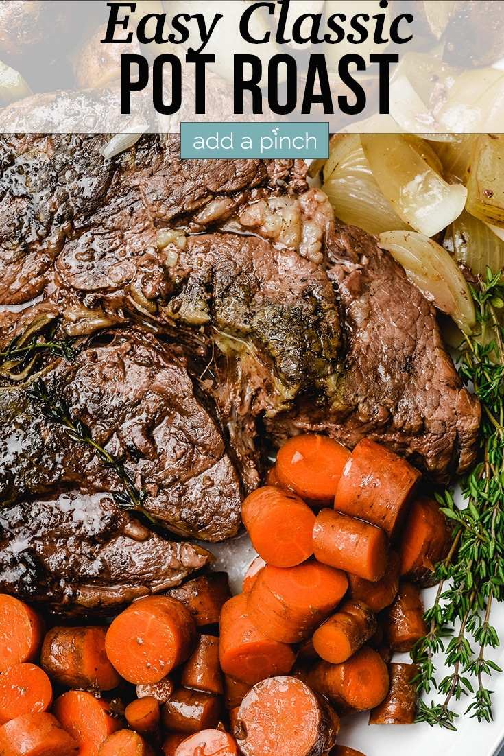 Pot Roast on serving platter with carrots, onions, potatoes and herbs - with text - addapinch.com