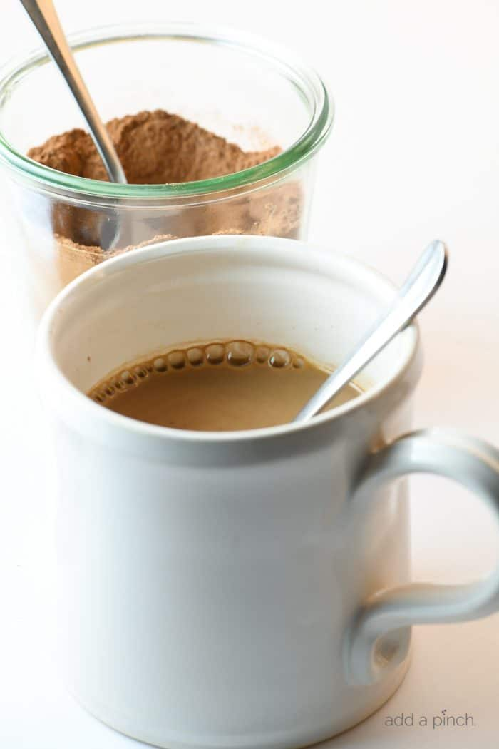Photograph of white mug filled with hot cocoa and a clear jar of hot cocoa mix behind it on a white counter. // addapinch.com