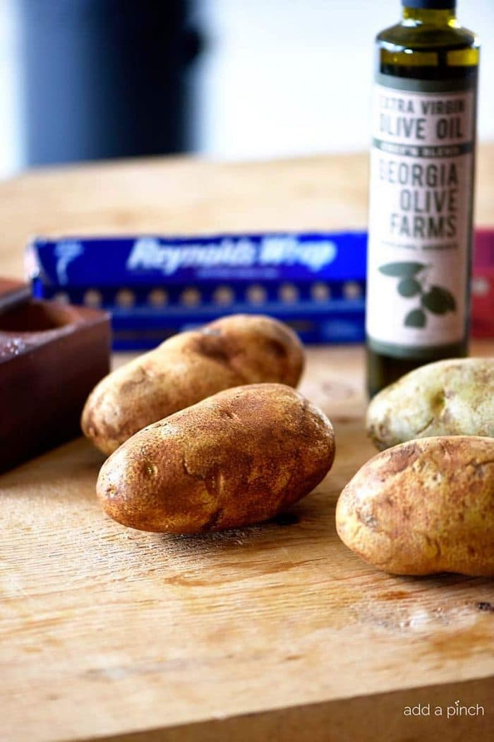 Photograph of russet potatoes, olive oil, salt and foil on a cutting board. // addapinch.com