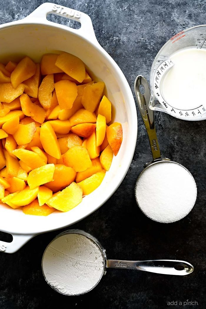 Overhead photograph of sliced fresh juicy peaches in a white bowl with filled measuring cups on a stone countertop. // addapinch.com
