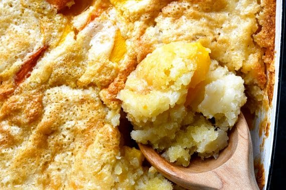 Overhead photograph of spoonful of easy peach cobbler in a white baking dish on a stone counter. // addapinch.com