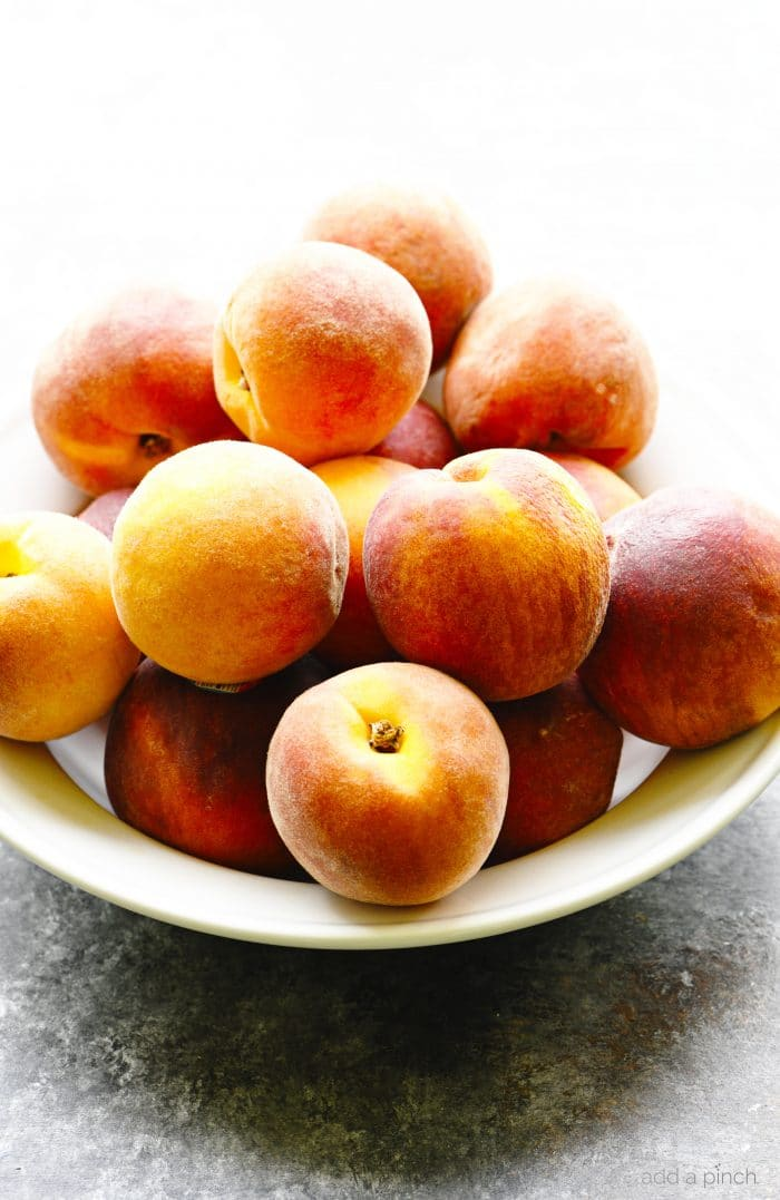 White bowl filled with fresh peaches on a stone countertop. // addapinch.com
